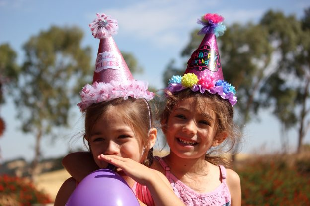 Two children with party hats and balloons